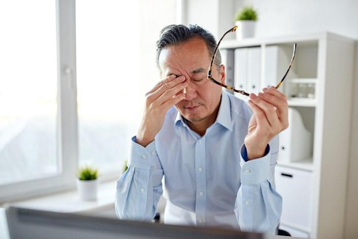 tired businessman with eyeglasses and laptop computer rubbing eyes at office