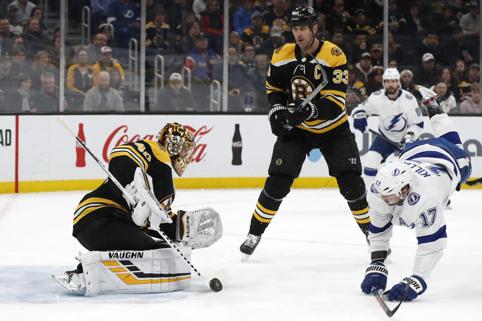 Boston Bruins goaltender Tuukka Rask, left, makes a save as defenseman Zdeno Chara (33) trips Tampa Bay Lightning's Alex Killorn during the first period of an NHL hockey game Saturday, March 7, 2020, in Boston. (AP Photo/Winslow Townson)
