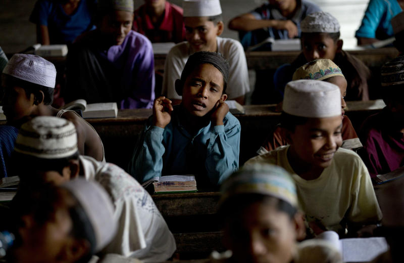 In this Sept. 18, 2013 photo, a Muslim boy learns the Quran by rote at Rohingya Village Madrassa in The' Chaung Village on the outskirts of Sittwe in Rakhine state, Myanmar. Because Rohingya children are no longer welcome in many government schools, the so-called Rohingya Village Madrassa has opened its doors to some of those boys and girls, teaching not just Islamic studies, as it did in the past, but Burmese and English. (AP Photo/Gemunu Amarasinghe)