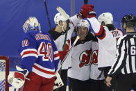 New Jersey Devils' Jack Hughes, middle rear, celebrates after a second-period goal against New York Rangers' Alexandar Georgiev, left, in an NHL hockey game Tuesday, Jan. 19, 2021, in New York. (Bruce Bennett/Pool Photo via AP)
