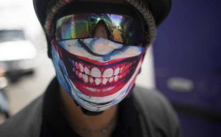 A man wears a mask featuring the smile of comic book character The Joker, amid the spread of the new coronavirus in Caracas, Venezuela, Monday, March 30, 2020. (AP Photo/Ariana Cubillos)