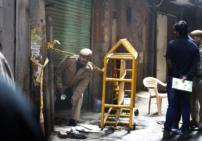 A policeman comes out from the only entrance of an ill-fated building which caught fire on Sunday, in New Delhi, India, Monday, Dec. 9, 2019. Authorities say an electrical short circuit appears to have caused a devastating fire that killed dozens of people in a crowded market area in central New Delhi. Firefighters fought the blaze from 100 yards away because it broke out in one of the area's many alleyways, tangled in electrical wire and too narrow for vehicles to access. (AP Photo/Manish Swarup)
