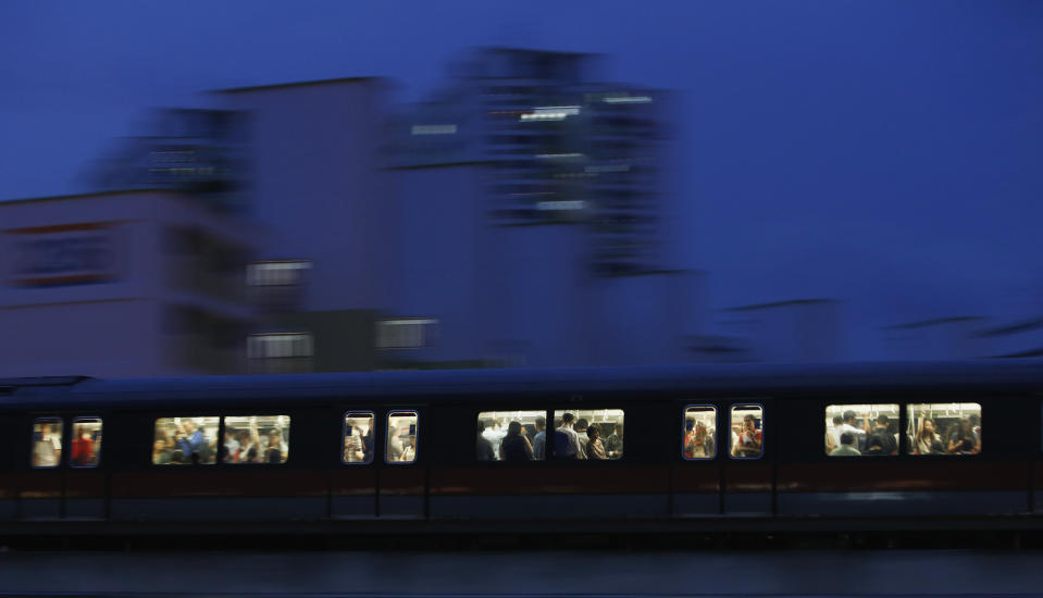 Commuters riding the train after office hours pass a public housing estate in Singapore May 5, 2014.  REUTERS/Edgar Su (SINGAPORE - Tags: REAL ESTATE BUSINESS TRANSPORT SOCIETY)