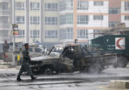 Afghan security personnel inspect the site of a bombing attack in Kabul, Afghanistan, Sunday, Dec. 20, 2020. The strong car bomb explosion rocked the capital Kabul city on Sunday morning, killing multiple people, said a government official. (AP Photo/Rahmat Gul)