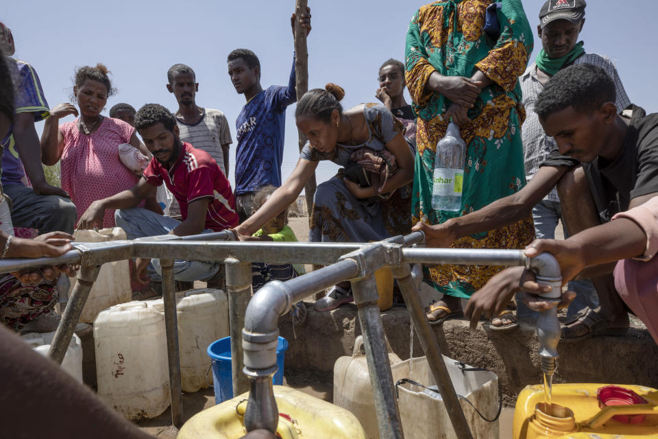 Elsa Tesfa Berhe, 26, center, a reproductive health official from Adwa, collects water a day after arriving from Humera to Hamdayet, eastern Sudan, near the border with Ethiopia, on March 16, 2021. Reusing gloves and rationing water, Berhe treated women secretly after Eritrean soldiers swept through health centers, looting even the beds and telling patients to leave. As she snuck out to deliver babies and treat the wounded, she saw people trying to bury bodies at the risk of being shot, or pouring alcohol on corpses in an attempt to hide the smell. (AP Photo/Nariman El-Mofty)