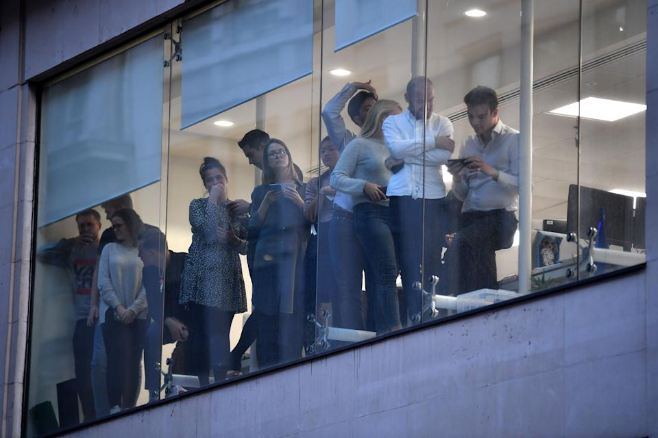 Office workers peer out of the windows of Leadenhall Market near London Bridge in the immediate aftermath. (Getty Images)
