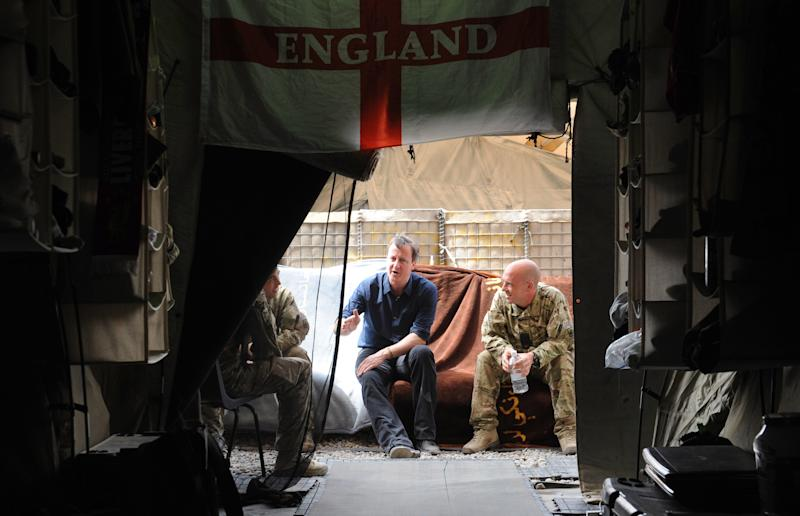 Britain's Prime Minister, David Cameron, centre, meets with unidentified British soldiers in their living quarters at Shawqat forward operating base in Helmand Province, Afghanistan, Wednesday July 18, 2012, during a surprise visit to the area. Earlier he met Afghan National Police chiefs in Lashkar Gah. (AP Photo/Stefan Rousseau, Pool)