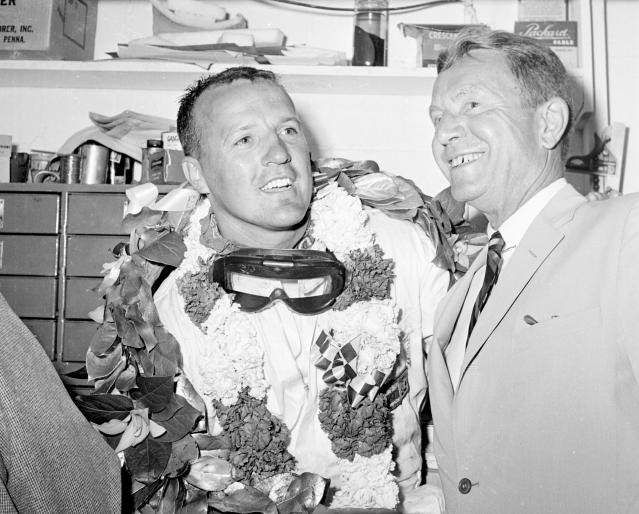 FILE - In this May 31, 1961, file photo, A.J. Foyt smiles in the garage area of the Indianapolis Motor Speedway after winning the Indy 500 for the first of four times. At right is Speedway president Tony Hulman. Indianapolis Motor Speedway and the IndyCar Series have been sold to Penske Entertainment Corp. in a stunning announcement that relinquishes control of the iconic speedway from the Hulman family after 74 years. (AP Photo/File)