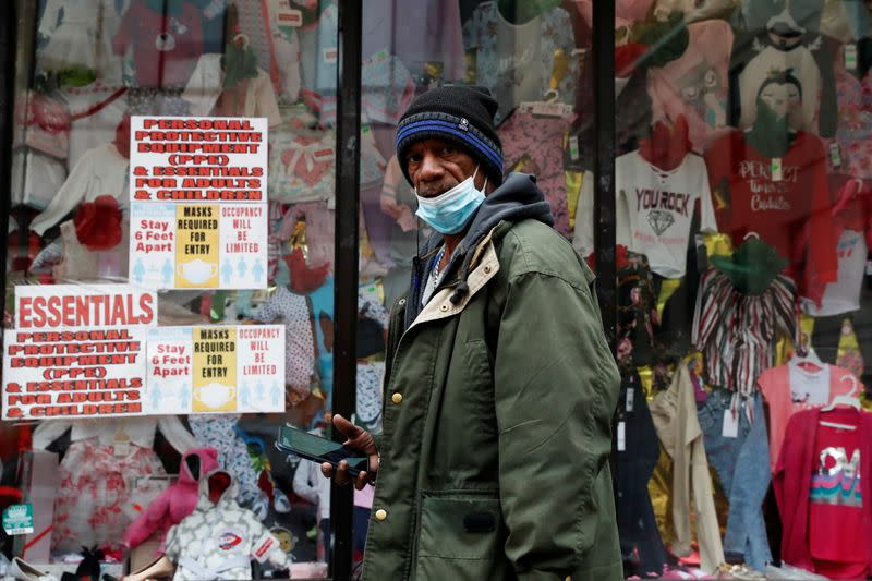 FILE PHOTO: A man wearing a protective face mask walks past a discount store, as the global outbreak of the coronavirus disease (COVID-19) continues, in Yonkers, New York