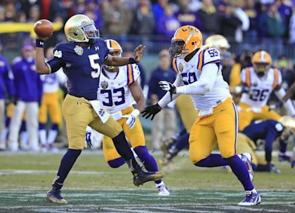 Notre Dame quarterback Everett Golson (5) gets a pass away as he is pressured by LSU defenders Jamal Adams (33) and Jermauria Rasco (59) in the first half of the Music City Bowl. (AP Photo/Mark Humphrey)
