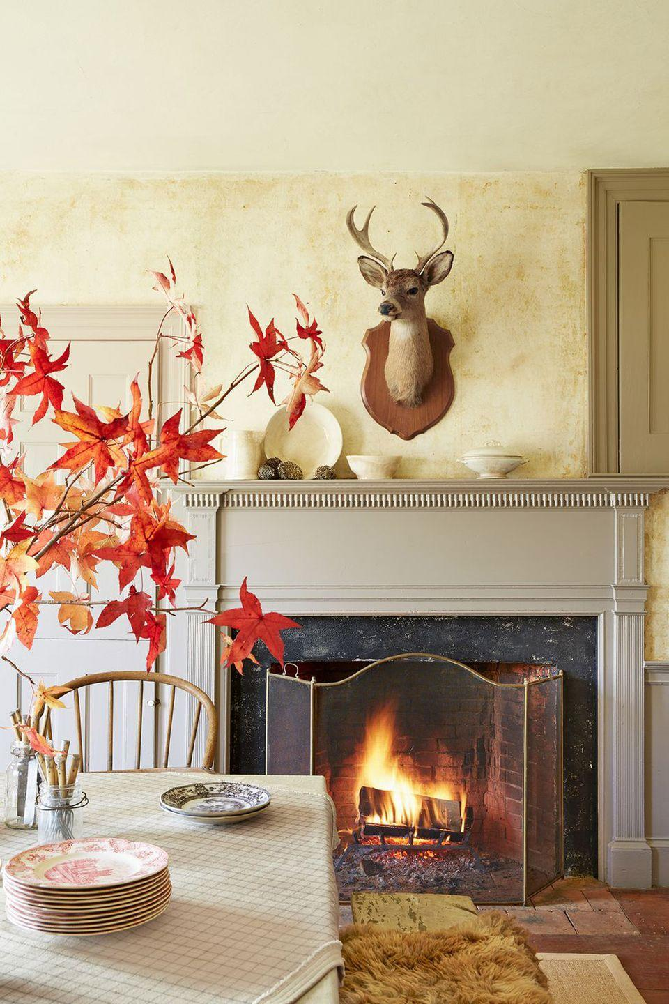 """<p>Get your home ready for both your dinner party and the fall season in general. Start by sprucing up your <a href=""""https://www.countryliving.com/diy-crafts/g2610/fall-door-decorations/"""" rel=""""nofollow noopener"""" target=""""_blank"""" data-ylk=""""slk:front door decorations"""" class=""""link rapid-noclick-resp"""">front door decorations</a> and then <a href=""""https://www.countryliving.com/home-design/decorating-ideas/advice/g1536/fall-decorating-ideas/"""" rel=""""nofollow noopener"""" target=""""_blank"""" data-ylk=""""slk:work your way inside."""" class=""""link rapid-noclick-resp"""">work your way inside.</a> You don't have to go overboard—a few smart <a href=""""https://www.countryliving.com/home-design/decorating-ideas/g2621/fall-porch-decorating/"""" rel=""""nofollow noopener"""" target=""""_blank"""" data-ylk=""""slk:autumn additions"""" class=""""link rapid-noclick-resp"""">autumn additions</a> can make a big impact. We love the look of these leafy branches in a vase, and the fire is a lovely touch as well.</p>"""