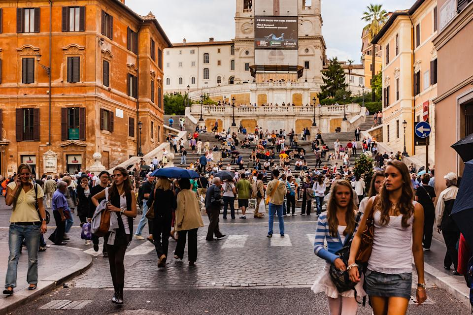 """Rome, Italy - October 11, 2007: Tourists throng the Piazza di Spagna (also called the Spanish Steps) in Rome; the Square is a 'must see' on the list of every tourist to the City of Rome. There has been a slight drizzle: some people use their umbrellas. The fountain in the middle of the Square is called Fontana della Baracaccia (translated, """"fountain of the old boat""""), built in 1629 -1629, is often credited to Pietro Bernini, father of his more famous son Gian Lorenzo Bernini. To the left of the photo are the famous Babington Tea Rooms. Photo shot in the late evening sunlight; horizontal format."""