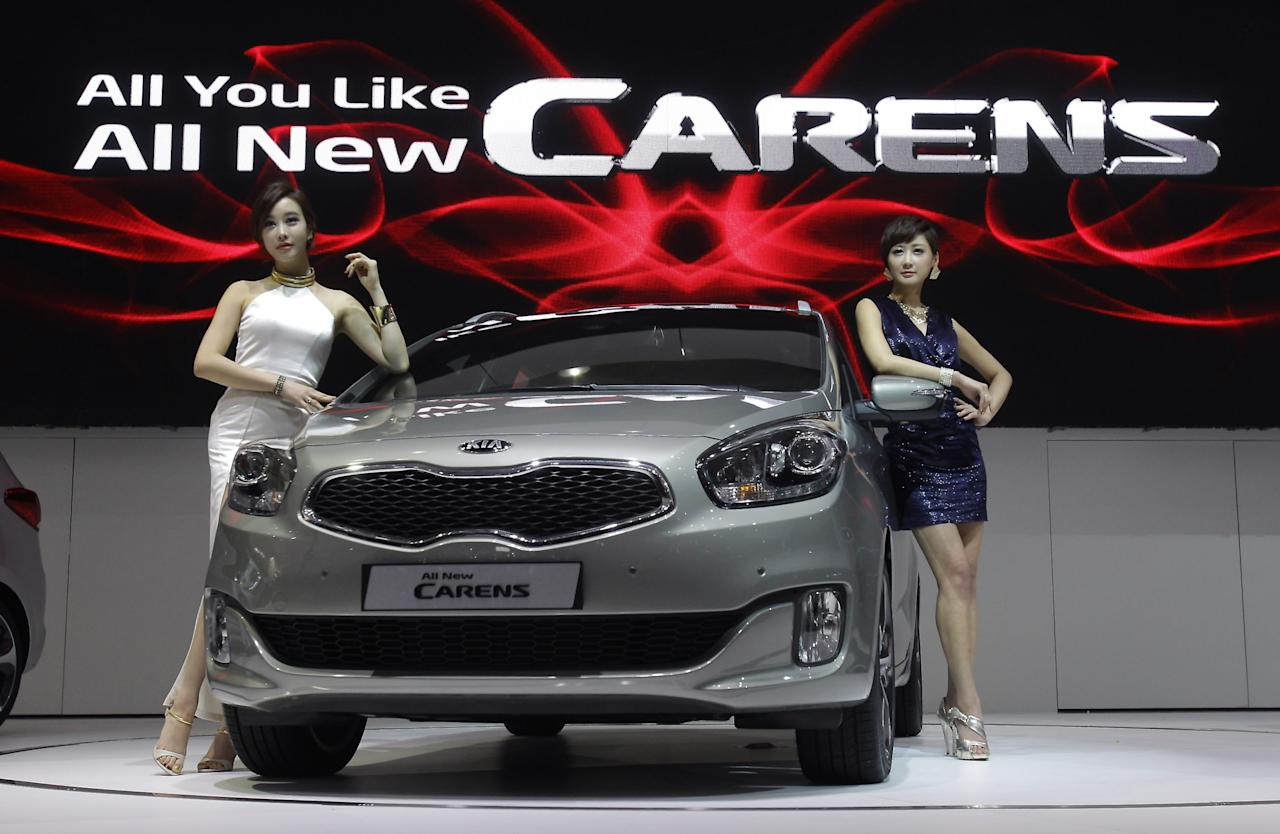 GOYANG, SOUTH KOREA - MARCH 28:  Models pose next to a new KIA Carens at the Seoul Motor Show 2013 on March 28, 2013 in Goyang, South Korea. The Seoul Motor Show 2013 will be held in March 29-April 7, featuring state-of-the-art technologies and concept cars from global automakers. The show is its ninth since the first one was held in 1995. About 384 companies from 14 countries, including auto parts manufacturers and tire makers, will set up booths to showcase trends in their respective industries, and to promote their latest products during the show.  (Photo by Chung Sung-Jun/Getty Images)