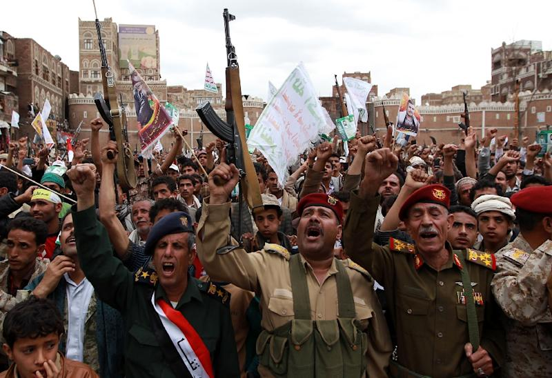 Members of the Yemeni security forces and tribal gunmen, both loyal to the Huthi movement, brandish their weapons on March 26, 2015