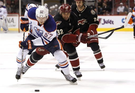 Edmonton Oilers' Anton Lander (57), of Sweden, gains control of the puck as Phoenix Coyotes' Michal Rozsival (32), of the Czech Republic, and Kyle Chipchura (24) move in to defend in the first period in an NHL hockey game Thursday, Dec. 15, 2011, in Glendale, Ariz.(AP Photo/Ross D. Franklin)