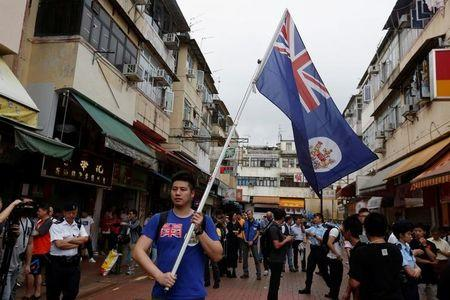 A local protester against mainland Chinese parallel traders carries a British Hong Kong colonial flag in Hong Kong