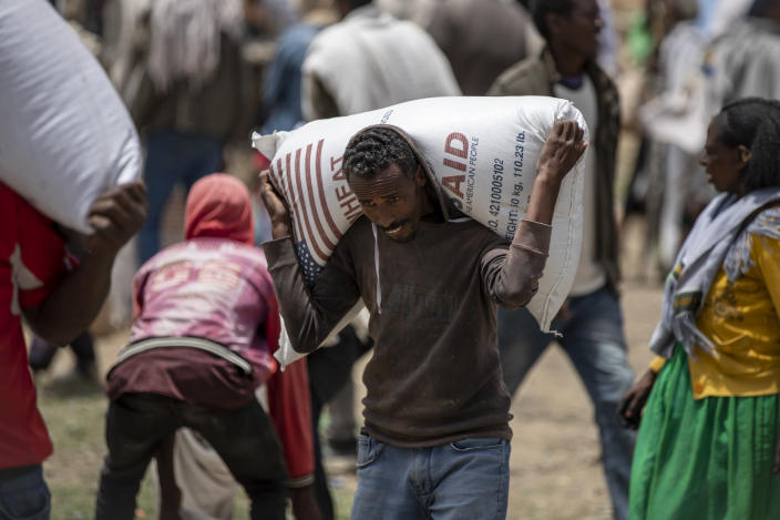 An Ethiopian man carries a sack of wheat on his shoulders to be distributed by the Relief Society of Tigray in the town of Agula, in the Tigray region of northern Ethiopia, on Saturday, May 8, 2021. In war-torn Tigray, more than 350,000 people already face famine, according to the U.N. and other humanitarian groups. It is not just that people are starving; it is that many are being starved, The Associated Press found. (AP Photo/Ben Curtis)