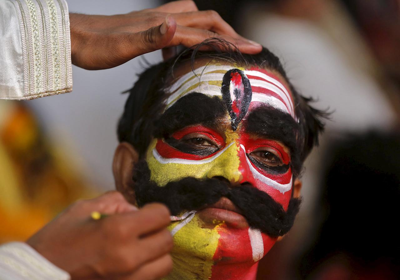"""An artist gets his make-up done backstage before performing during Ramlila, a re-enactment of the life of Lord Rama, during Dussehra festival celebrations in Mumbai, India, October 22, 2015. Effigies of the 10-headed Demon King """"Ravana"""" are burnt on Dussehra, the Hindu festival that commemorates the triumph of Hindu god Rama over the Ravana, marking the victory of good over evil. REUTERS/Shailesh Andrade"""