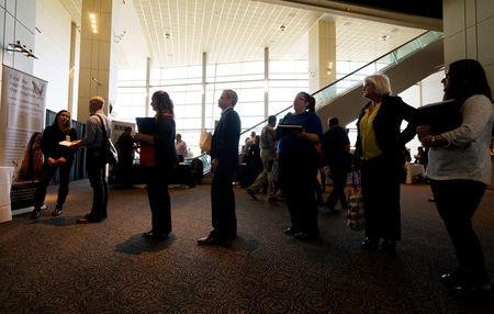Job seekers wait to talk to a recruiter  at a health care job fair sponsored by the Colorado Hospital Association in Denver