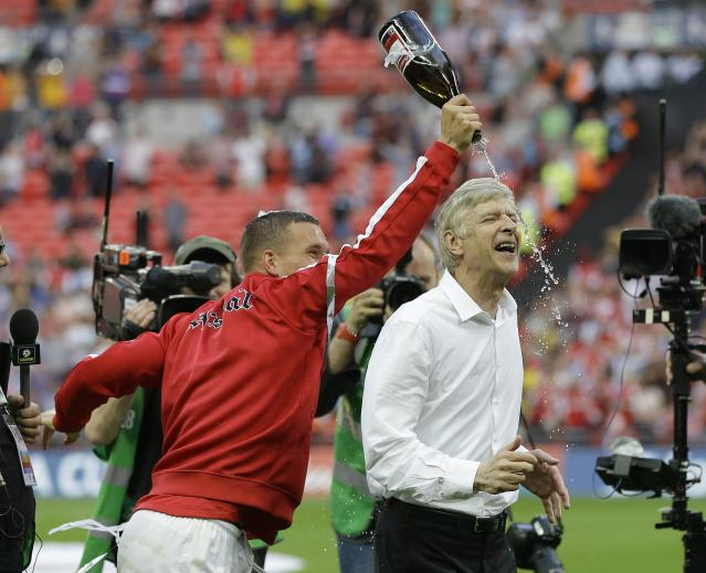 Arsenal's coach Arsene Wenger is doused with champagne by Lukas Podolski as they celebrate after winning the English FA Cup final soccer match between Arsenal and Hull City at Wembley Stadium in London, Saturday, May 17, 2014. Arsenal won 3-2 after extra-time. (AP Photo/Kirsty Wigglesworth)