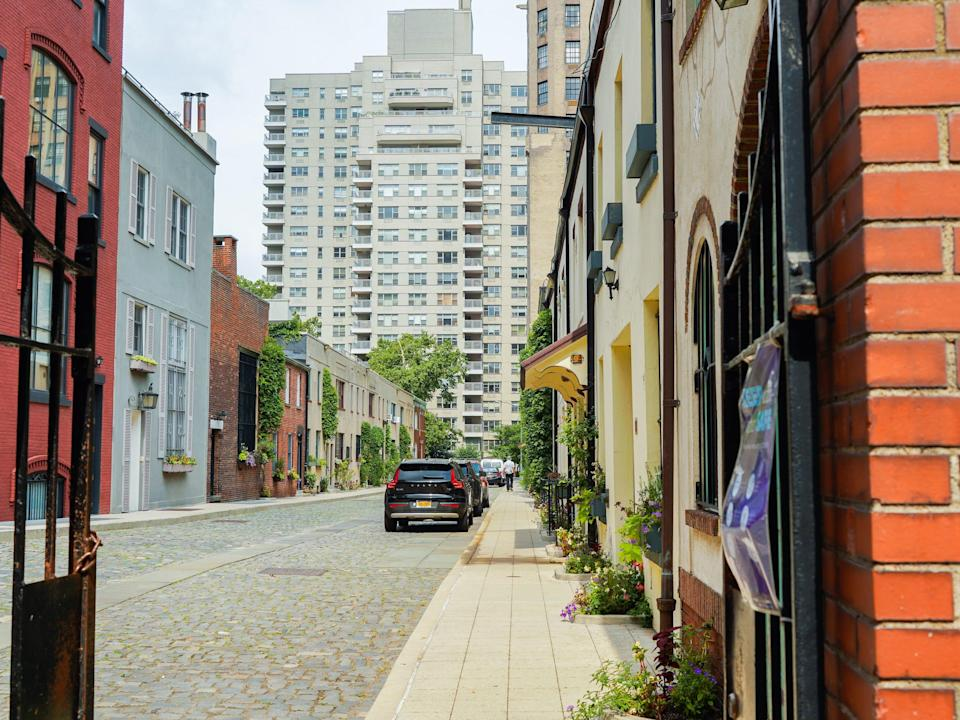 A red brick gated cobblestone street lined with mews.