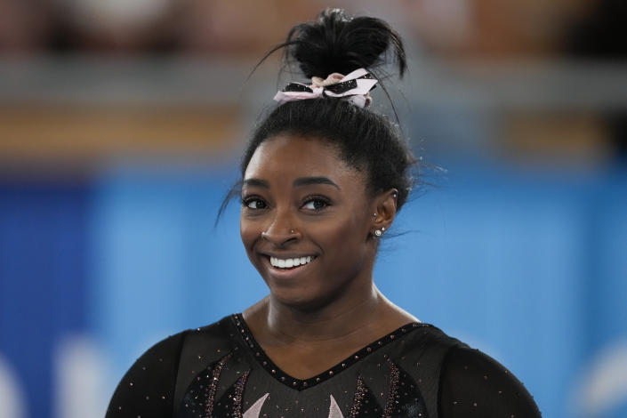 Simone Biles of the United States smiles as she trains for artistic gymnastics at Ariake Gymnastics Centre ahead of the 2020 Summer Olympics, Thursday, July 22, 2021, in Tokyo, Japan. (AP Photo/Ashley Landis)