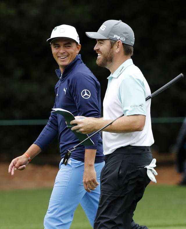 Rickie Fowler of the U.S. (L) and Louis Oosthuizen of South Africa walk down the first fairway during third round play of the 2018 Masters golf tournament at the Augusta National Golf Club in Augusta, Georgia, U.S. April 7, 2018. REUTERS/Mike Segar