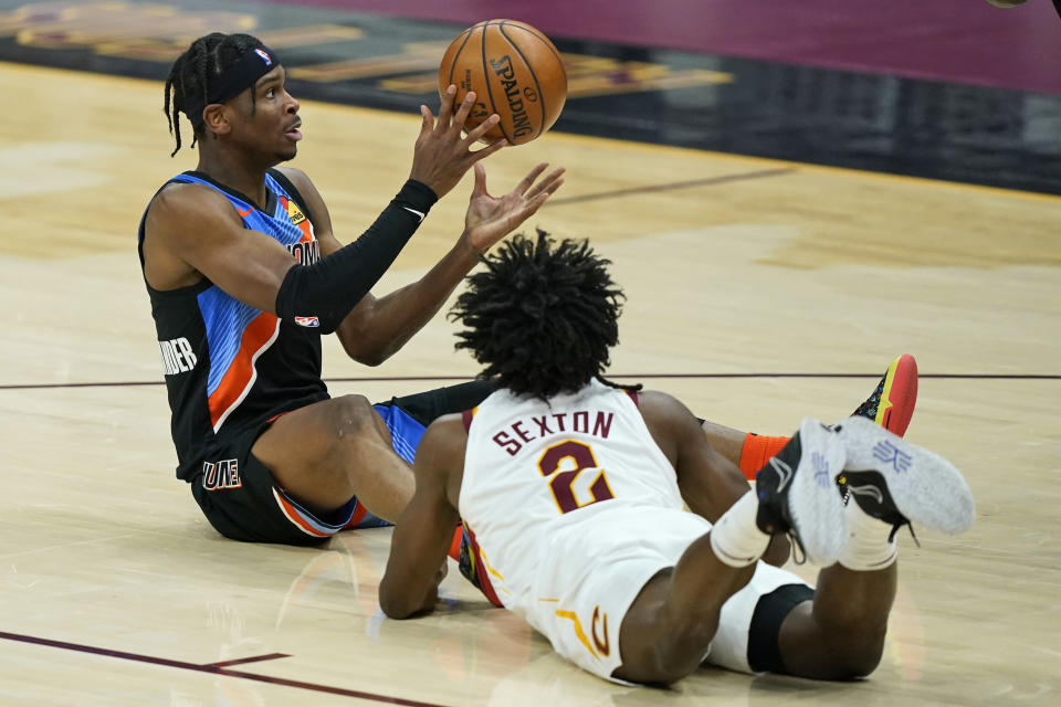 Oklahoma City Thunder's Shai Gilgeous-Alexander, left, passes the ball as Cleveland Cavaliers' Collin Sexton watches in the first half of an NBA basketball game, Sunday, Feb. 21, 2021, in Cleveland. (AP Photo/Tony Dejak)