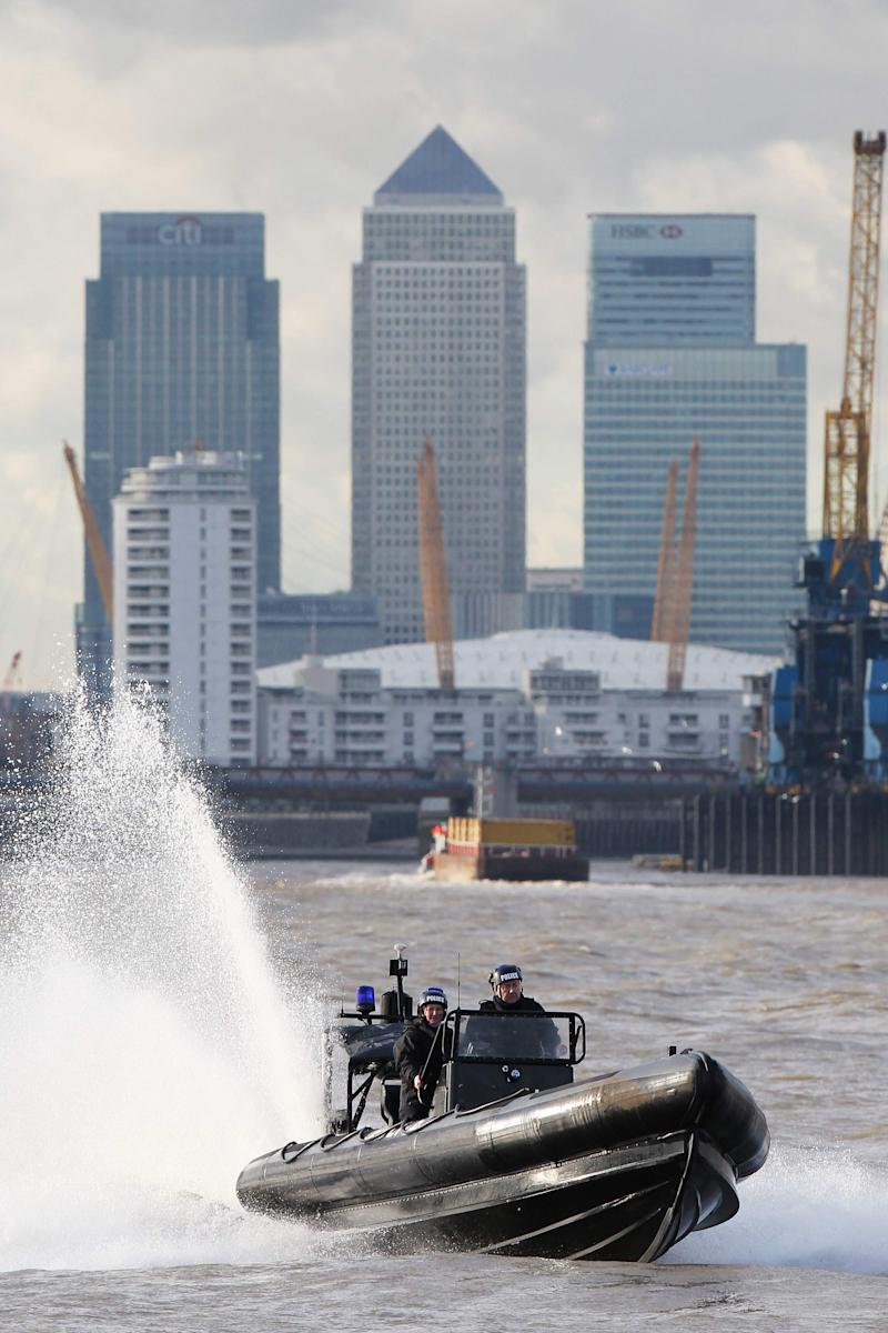 Members of the Metropolitan Police Marine Policing Unit (MPU) perform an exercise for the media on the River Thames in London January 19, 2012. The MPU have been training with Royal Marines from 539 Assault Squadron (539 ASRM) in preparation for providing security during the London 2012 Olympic Games. REUTERS/Finbarr O'Reilly (BRITAIN - Tags: MILITARY POLITICS SOCIETY SPORT OLYMPICS)