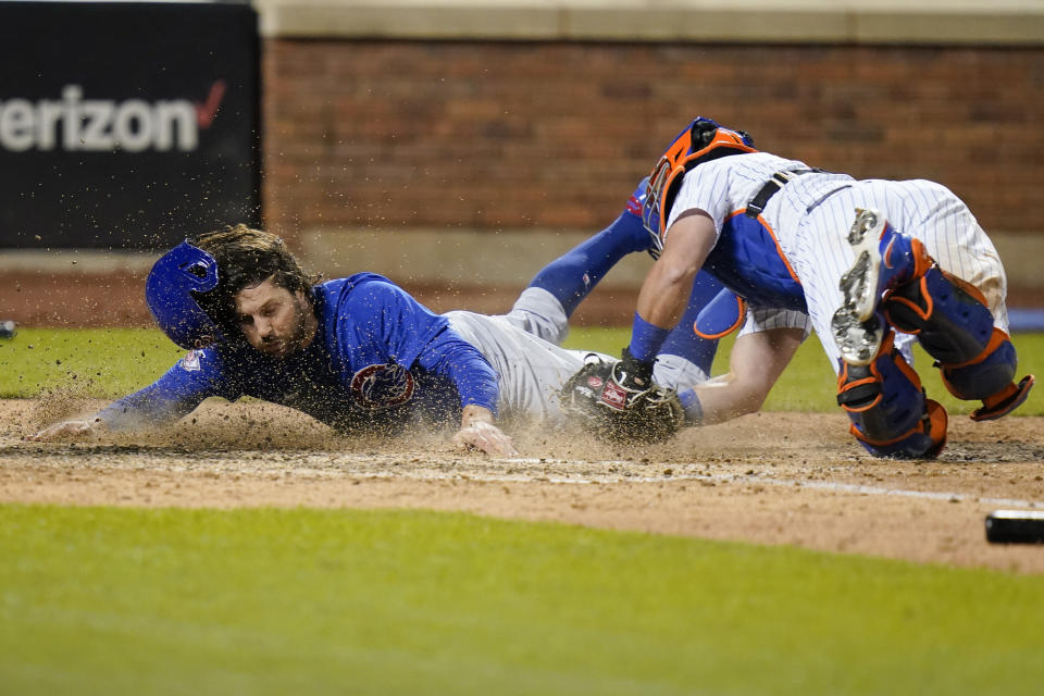 New York Mets catcher James McCann, right, tags out Chicago Cubs' Jake Marisnick (6) at home plate during the ninth inning of a baseball game Tuesday, June 15, 2021, in New York. (AP Photo/Frank Franklin II)