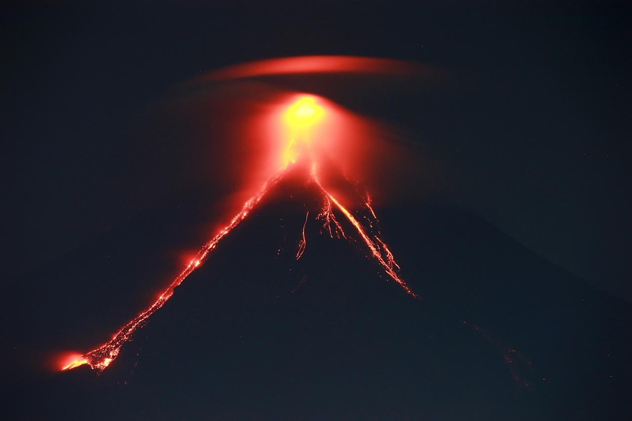 <p>This photo taken on January 15, 2018 shows lava cascading the slopes of Mayon volcano as it erupts, as seen from Legazpi City in Albay province south of Manila. Spectacular lava 'fireworks' shooting from its crater are drawing tourists to the Philippines' most active volcano, authorities said as scientists warned of a potential dangerous eruption within days. (Photo by CHARISM SAYAT/AFP/Getty Images) </p>