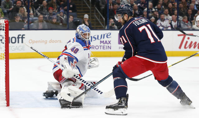 New York Rangers' Alexandar Georgiev, left, makes a save against Columbus Blue Jackets' Nick Foligno during the second period of an NHL hockey game Thursday, Dec. 5, 2019, in Columbus, Ohio. (AP Photo/Jay LaPrete)