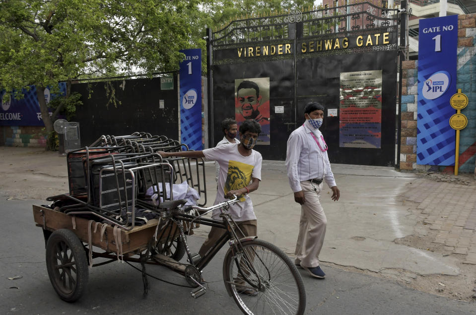 A worker carries chairs on a cycle rickshaw after dismantling a temporary security installation outside Arun Jaitley Stadium, one of the six venues of Indian Premier League 2021, in New Delhi, India, Tuesday, May 4, 2021. The Indian Premier League was suspended indefinitely on Tuesday after players or staff at three clubs tested positive for COVID-19 as nationwide infections surged. (AP Photo/Ishant Chauhan)