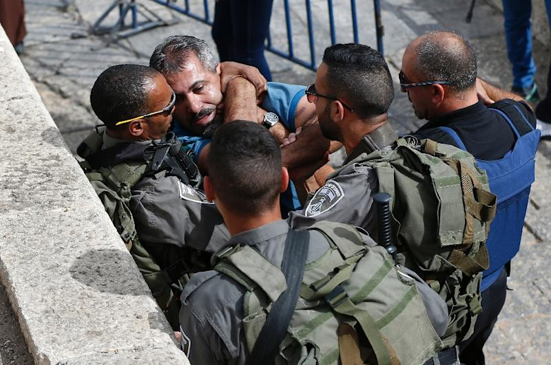 Israeli police scuffle with a Palestinian man at the Damascus Gate at the entrance of the Old City in east Jerusalem before the Friday prayer, on October 23, 2015 (AFP Photo/Ahmad Gharabli)