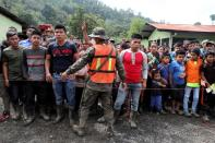 People stand at a school used as temporary shelter for residents of neighbouring villages affected by mudslides, in the village of Santa Elena