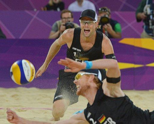 Germany's right blocker Jonas Reckermann (foreground) dives to reach the ball as teammate Julius Brink looks on