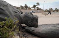 An Iraqi walks past a dismantled bronze statue of Iraqi dictator Saddam Hussein in Baghdad on April 13, 2003