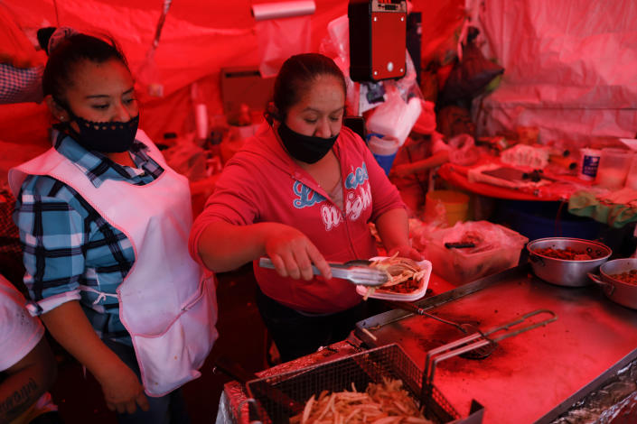 A vendor serves up tacos on disposable plates, at a street stand in central Mexico City, Friday, Jan. 1, 2021. The few street food vendors out working on New Year's Day amid the COVID-19 pandemic said they were either unaware of or were still figuring out how to comply with a broad ban on single-use containers, forks, straws, and other ubiquitous items that took effect Friday in Mexico's capital, one of the world's largest cities, after more than a year of preparation. (AP Photo/Rebecca Blackwell)