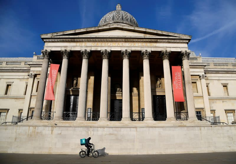FILE PHOTO: Deliveroo rider cycles past the closed National Gallery in London