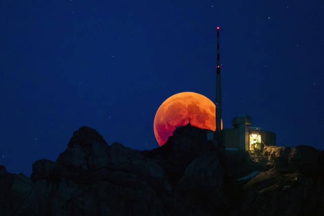 <p>The moon turns red during a total lunar eclipse, behind the Saentis in Luzern, Switzerland, Friday, July 27, 2018. (Photo: Christian Merz/Keystone via AP) </p>