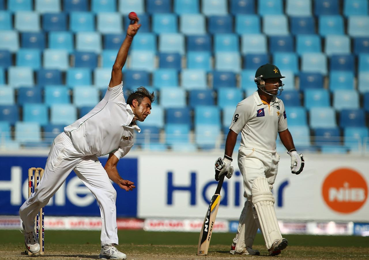 Bowler Imran Tahir (L) of South Africa bowls as batsman Asad Shafiq of Pakistan looks on during the fourth day of the second Test cricket match between Pakistan and South Africa in Dubai on October 26, 2013. AFP PHOTO/MARWAN NAAMANI        (Photo credit should read MARWAN NAAMANI/AFP/Getty Images)