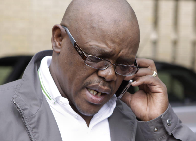 African National Congress spokesman Keith Khoza on a mobile phone after making a statement on camera, on the health of former South African President Nelson Mandela in Johannesburg, Saturday, Feb. 25, 2012. Mandela was hospitalized Saturday with a stomach ailment, according to a government statement issued about the 93-year old beloved anti-apartheid icon. (AP Photo/Denis Farrell)