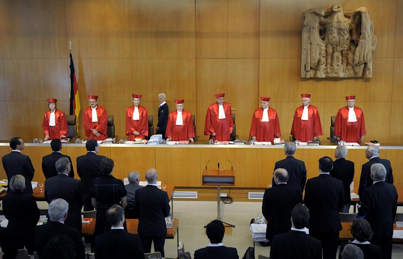 """Judges of the German Federal Constitutional Court from left:  Monika Hermanns, Herbert Landau, Gertrude Luebbe-Wolff, Udo di Fabio, Presiding Judge Andreas Vosskuhle, Rudolf Mellinghoff, Michael Gerhardt, and Peter Michael Huber stand in a courtroom of the Constitutional Court in Karlsruhe, southern Germany Tuesday July 5, 2011. Germany's finance minister Wolfgang Schaeuble defended the rescue packages for Greece and other eurozone countries at a supreme court hearing Tuesday, as opponents argued that the bailouts violated both German and European law. Wolfgang Schaeuble told the Federal Constitutional Court that """"the stability of the euro is of paramount significance."""" He pointed to the risk of financial instability across Europe and beyond at the time when the government signed on to the initial Greek rescue of May 2010 and also the wider eurozone fund created shortly afterward.  (AP Photo/dapd/ Ronald Wittek)"""
