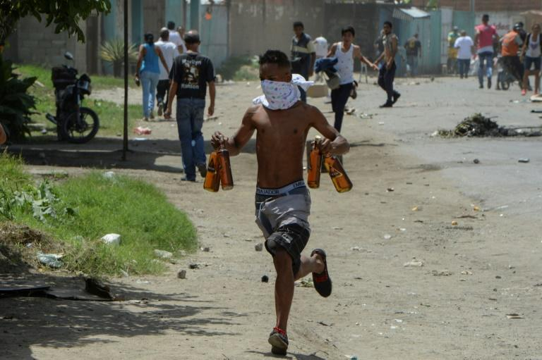 A young man carries stolen alcohol bottles after looting a supermarket in Maracay, Venezuela, as the country remains gripped by violence amid food shortages and political unrest