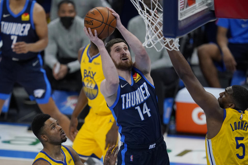 Oklahoma City Thunder guard Svi Mykhailiuk (14) shoots between Golden State Warriors forward Kent Bazemore, left, and center Kevon Looney (5) in the first half of an NBA basketball game Wednesday, April 14, 2021, in Oklahoma City. (AP Photo/Sue Ogrocki)