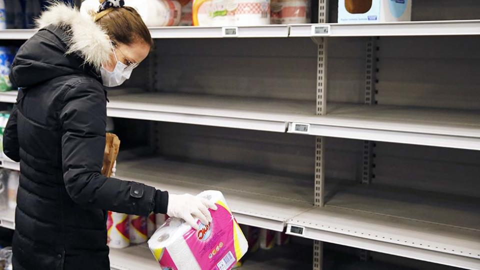 Woman in France holds toilet paper in front of empty shelf in supermarket. she wears gloves and facemask.