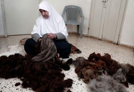 Ezzeya Daraghmeh, an 82-year-old Palestinian woman who said she has kept parts of her hair she cut over 67 years, stuffs a pillow with her hair in the West Bank town of Tubas January 2, 2018. Picture taken January 2, 2018. REUTERS/Raneen Sawafta