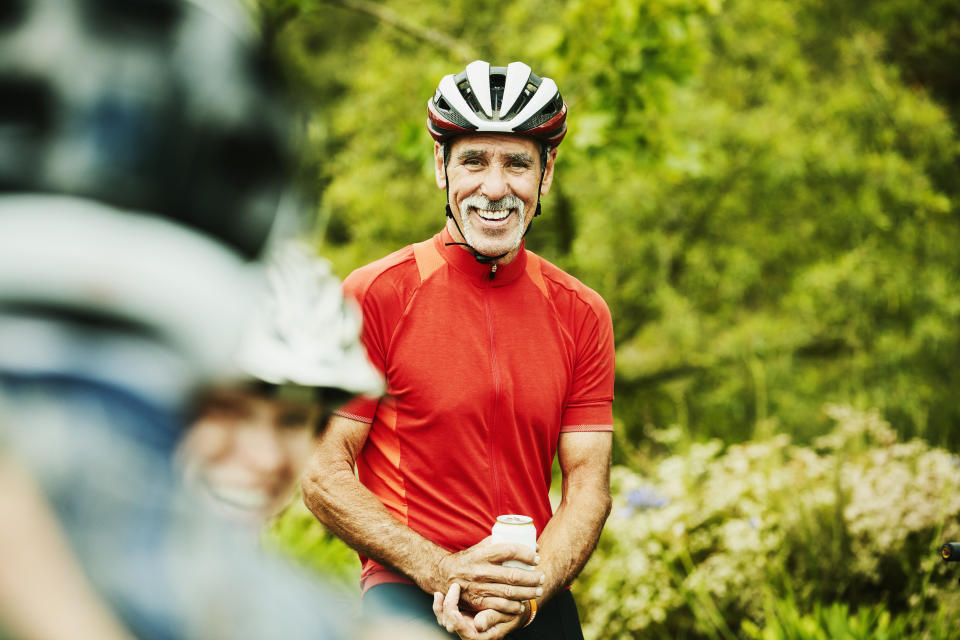 Smiling senior man sharing beers with friends after mountain bike ride