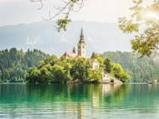 """There's a reason Lake Bled is one of <a href=""""https://www.cntraveler.com/gallery/best-places-to-visit-in-slovenia?mbid=synd_yahoo_rss"""" rel=""""nofollow noopener"""" target=""""_blank"""" data-ylk=""""slk:Slovenia"""" class=""""link rapid-noclick-resp"""">Slovenia</a>'s most popular sites. With its emerald waters, views of the Julien Alps, and Disney-like castle on a hill, you won't be short of picture-perfect views. But it's most beautiful site is the Church of the Assumption on a tiny island in the middle of the lake, a charming, 17th-century building that even has a """"wishing bell"""" that guests can ring."""