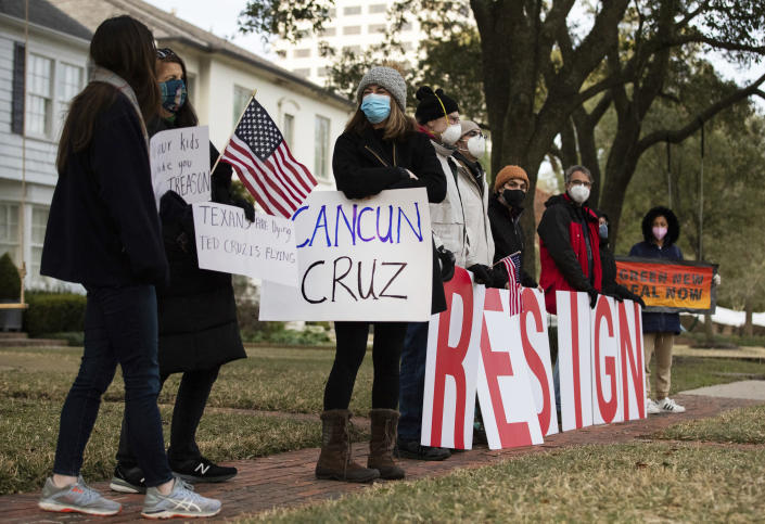 "Demonstrators stand in front of Texas Sen. Ted Cruz's home demanding his resignation, Thursday, Feb. 18, 2021, in Houston. The Republican senator said his family vacation to Mexico was ""obviously a mistake"" as he returned stateside Thursday following an uproar over his disappearance during a deadly winter storm. (Marie D. De Jesús/Houston Chronicle via AP)"